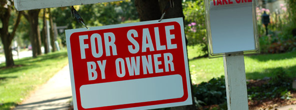 A for sale by owner sign hanging from a wooden post in the front yard of a home