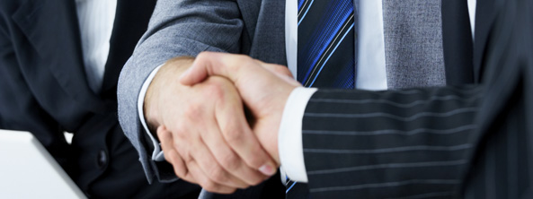 Handshake and teamwork. Two businesspeople shanking hands in a light and modern office environment.